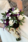 The bouquet consisted of dark purple dalias, cream roses, fragrant stephanotis, salvia, oak leaves, and sage. Gently tied together with satin ribbon and tiny photo keepsakes of departed loved ones.